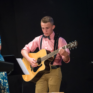 christian school musical boy playing guitar