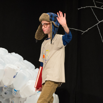 a boy waving his hand in a school play for christian school art